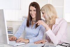 Pret op kantoor: twee jonge glimlachende vrouwelijke medewerkers. Stock Afbeeldingen