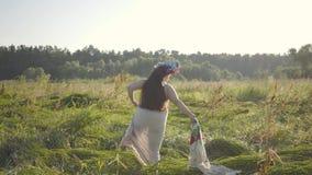 Pret te zware vrouw die traditionele sjaal opstijgen en op het hoge gras op de zomergebied vallen Mooi landschap stock footage