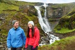 Pret van het wandelings de actieve paar door waterval IJsland royalty-vrije stock afbeeldingen