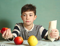 Pretee boy hold fast food roll and apples. Preteen handsome boy hold fast food roll and apples make choice Stock Images