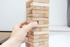 Preteen кавказский мальчик играя деревянную настольную игру башни блока для практиковать его физические и умственные навык и разв стоковые фотографии rf