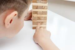 Preteen кавказский мальчик играя деревянную настольную игру башни блока для практиковать его физические и умственные навык и разв стоковые фото