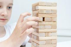 Preteen кавказский мальчик играя деревянную настольную игру башни блока для практиковать его физические и умственные навык и разв стоковое изображение rf