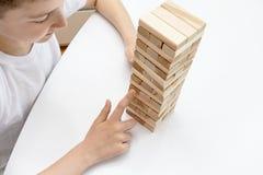 Preteen кавказский мальчик играя деревянную настольную игру башни блока для практиковать его физические и умственные навык и разв стоковые изображения