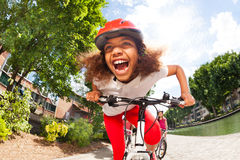 Preteen African girl racing in full speed. Portrait of preteen African girl in helmet racing in full speed, enjoying riding her bicycle in summer town Royalty Free Stock Image