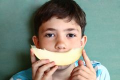Preteen  beautiful boy with long dark hair with slice of melon ma Stock Photo