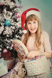 Preteen blond girl in santa hat open present box Royalty Free Stock Images