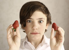 Preteen boy acting grimacing with two strawberries Stock Photos