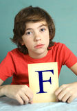 Preteen boy with bad mark F - failure Royalty Free Stock Images