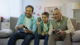 Preteen boy cheering for dad and granddad playing video game, pappy time, hobby. Stock footage stock video footage