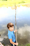 Preteen boy with fishing self made rode. Preteen handsome boy with fishing self made rode on the summer lake background close up photo Stock Photo
