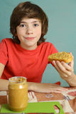 Preteen boy hold peanut butter with nut pieces Royalty Free Stock Photos