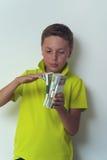 Preteen boy holding dollar bills in hands Royalty Free Stock Photos
