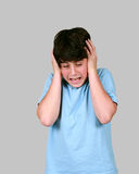Preteen boy holding his head Stock Photography
