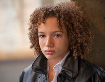 Preteen Boy in Leather Jacket. A portrait of a preteen boy with curly hair, freckles, and green eyes Royalty Free Stock Image