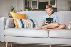 Preteen boy losted in computer game. Sits at home on coze sofa, uses gamepad with smartphone stock photos