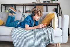 Free Preteen Boy Lying At Home On Cozy Sofa Dressed Casual Jeans And Shirt. Listening To Music And Chatting Using Wireless Headphones Stock Photos - 188429283
