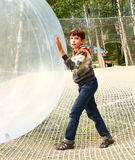 Preteen boy play huge ball in outdoor sport open air activity park Royalty Free Stock Photo