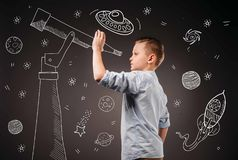 preteen boy pretending to be a astronomer with drawn telescope and UFO, planets, spaceship Stock Image