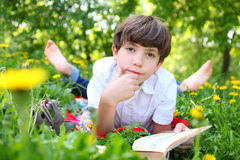 Preteen boy reading book outdoor spring. Preteen boy reading book in the blossoming spring meadow with dandelions close up portrait Royalty Free Stock Photo