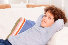 Preteen boy relaxing on white comfortable sofa. Portrait of preteen boy relaxing on white comfortable sofa indoors and looking at camera Stock Image