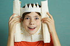 Preteen boy with rich imagination make king from thin bread Royalty Free Stock Photo