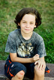 Preteen boy. With scraped knee sitting outdoors Royalty Free Stock Photography