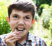 Preteen boy show teeth with magnifying glass. Preteen handsome boy show teeth with magnifying glass Royalty Free Stock Images