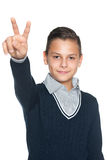 Preteen boy shows victory sign Stock Photos