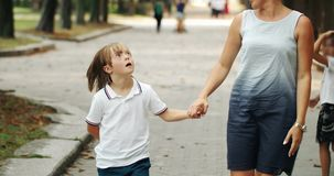 Down Syndrome Boy Walking with Mother. Preteen boy suffering Down syndrome holding mother`s hand and walking in park, importance of communication stock footage
