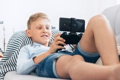 Preteen boy use gamepad with smartphone plays games lying on the cozy sofa in the home living room royalty free stock images