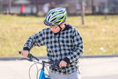 Preteen boy walking bicycle looking at handlebars, getting ready. To ride, healthy activity concept Royalty Free Stock Photography