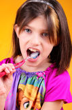Preteen brushing teeth. A colorful closeup of a little dark haired girl seriously brushing her teeth. Shallow depth of field on orange background Stock Images