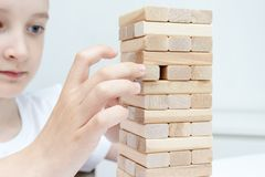 A preteen caucasian boy playing wooden block tower board game for practicing his physical and mental skill and entertainment royalty free stock image