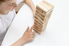 A preteen caucasian boy playing wooden block tower board game for practicing his physical and mental skill and entertainment stock images