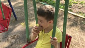 A preteen caucasian boy sitting on a swing and eating tasty delicious icecream on the children`s playground in summer. Time stock footage