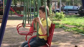 A preteen caucasian boy sitting on a swing and eating tasty delicious icecream on the children`s playground in summer. Time stock video footage