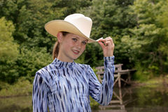 Preteen Caucasian girl. About 12 years old: dressed in white cowboy hat and blue long sleeve shirt outdoors, with long hair and freckles Stock Photo