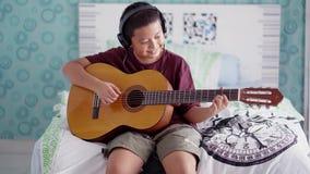 Preteen chłopiec bawić się gitarę w sypialni zbiory