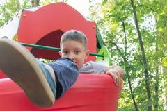 Preteen chłopiec bawić się na dziecka ` s boisku obraz stock