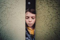 Preteen chłopiec na ulicie w dużym mieście obok wieżowa samotnie zdjęcie stock