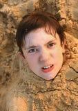 Preteen chłopiec przystojna głowa w piasku Obrazy Stock