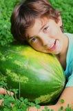 Preteen chłopiec uśmiechniętego uściśnięcia cały wodny melon Obraz Stock