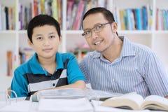Preteen chłopiec uczeń z jego nauczycielem w bibliotece Fotografia Royalty Free