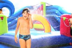 Preteen chłopiec w na wolnym powietrzu aqua parku w wodnym trampoline sztuki wodnego pistoletu gry wojennej zakończeniu up Zdjęcia Royalty Free