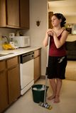 Preteen Chore. Preteen girl looking bored with her job -- mopping the kitchen floor Royalty Free Stock Image