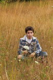 Preteen Country Boy. A young preteen country boy sitting in a field of tall grass and wild flowers. Shallow depth of field. Copy Space Royalty Free Stock Image