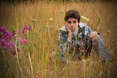 Preteen Country Boy in Field. A young country boy sitting in a field of tall grass and wild flowers. Shallow depth of field. Copy Space Stock Photo
