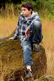 Preteen Country Boy Sitting on a Rock. A young dark haired preteen country boy sitting on a large rock in a  field of tall grass wearing a plaid hoodie. Shallow Stock Photography