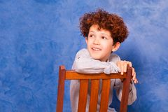 Preteen curly boy sits backwards on wooden chair. Portrait of preteen curly boy sitting backwards on wooden chair against blue background with copy-space Royalty Free Stock Image